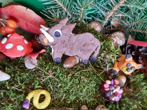 """Praca wykonana na szkolny konkurs """"Makieta jesiennego lasu"""" - na podstawie z mchu umieszczono figurki zwierząt z plasteliny - dzika, węża oraz liska."""