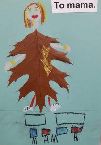 """Zdjęcie pracy wykonanej przez ucznia oddziału przedszkolnego. Na niebieskim tle naklejony brązowy liść z dorysowaną głową z brązowo-blond włosami oraz rękoma i nogami. W prawym górnym rogu wklejony napis: """"To mama."""". U dołu narysowane dwa prostokąty, pod nimi cztery kwadraty pokolorowane na przemian niebieską i czerwoną kredką a pod nimi odręczny napis mama."""