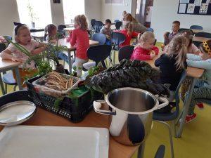 Uczniowie z oddziału przedszkolnego siedzą przy stolikach w szkolnej stołówce. Na pierwszym planie widzimy stół z ustawionym na nim stalowym garnkiem oraz plastikową skrzynkę z warzywami.