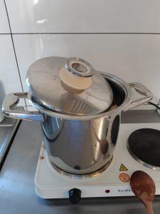 Na dwupalnikowej kuchence stoi stalowy garnek częściowo zakryty pokrywką. O kuchenkę oparta jest drewniana łyżka.