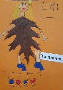 """Zdjęcie pracy wykonanej przez ucznia oddziału przedszkolnego. Na pomarańczowym tle naklejony brązowy liść z dorysowaną głową z blond włosami oraz rękoma i nogami. W prawym górnym rogu odręczny napis EMI a poniżej wklejony napis: """"To mama."""". U dołu narysowane dwa prostokąty, pod nimi cztery kwadraty pokolorowane na przemian niebieską i czerwoną kredką a pod nimi odręczny napis mama."""