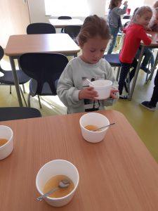 Uczennica oddziału przedszkolnego pochyla się nad trzymaną w dłoniach styropianową miseczką. Przed nią na stoliku stoją jeszcze trzy takie miseczki z łyżeczkami i częściowo wypełnione musem jabłkowym.