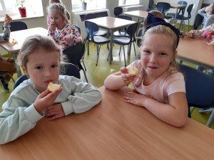 Dwie uczennice siedzą przy stoliku i pozują do zdjęcia podczas jedzenia jabłek. W tle widać inne dzieci przy stolikach.