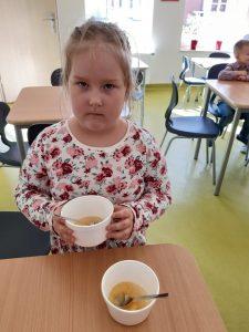 Uczennica oddziału przedszkolnego trzyma w dłoniach styropianową miseczkę. Przed nią na stoliku stoi jeszcze jedna taka miseczką z łyżeczką w środku i częściowo wypełniona musem jabłkowym.