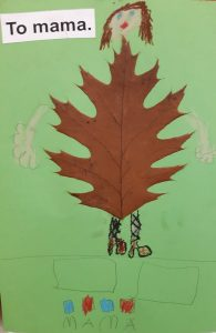 """Zdjęcie pracy wykonanej przez ucznia oddziału przedszkolnego. Na zielonym tle naklejony brązowy liść z dorysowaną głową z brązowymi włosami oraz rękoma i nogami. W lewym górnym rogu wklejony napis: """"To mama."""". U dołu narysowane dwa prostokąty, pod nimi cztery kwadraty pokolorowane na przemian niebieską i czerwoną kredką a pod nimi odręczny napis mama."""