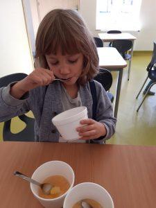 Uczeń oddziału przedszkolnego siedzi przy stoliku i je łyżeczką mus jabłkowy ze styropianowej miseczki. Przed nim na stoliku stoja jeszcze dwie takie miseczki z musem i łyżeczkami w środku.