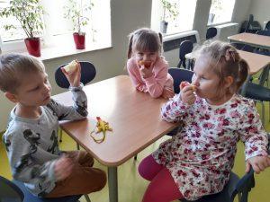 Troje uczniów oddziału przedszkolnego siedzi przy stoliku i je jabłka.