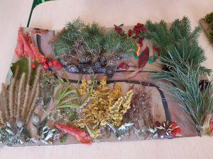 """Praca wykonana na szkolny konkurs """"Makieta jesiennego lasu"""" - na kartce z bloku narysowana brązowa gałąź wokół której przyklejono szyszki, gałązki i różne fragmenty roślin."""