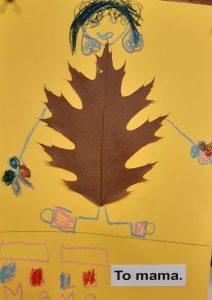 """Zdjęcie pracy wykonanej przez ucznia oddziału przedszkolnego. Na żółtym tle naklejony brązowy liść z dorysowaną głową z czarnymi włosami oraz rękoma i nogami. W prawym dolnym rogu wklejony napis: """"To mama."""". Obok niego narysowane dwa prostokąty, pod nimi cztery kwadraty pokolorowane na przemian niebieską i czerwoną kredką a pod nimi odręczny napis mama."""