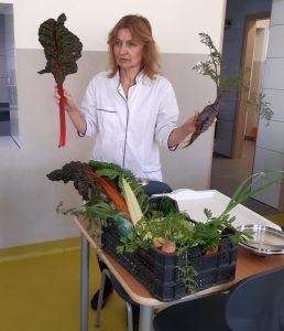 Wychowawczyni oddziału przedszkolnego stoi w białym kitlu i trzyma w jednej dłoni buraka a w drugiej jego liść. Przed nią na stoliku stoi wypełniona warzywami skrzynka.