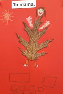 """Zdjęcie pracy wykonanej przez ucznia oddziału przedszkolnego. Na czerwonym tle naklejony brązowy liść z dorysowaną głową z brązowymi włosami oraz rękoma i nogami. W lewym górnym rogu wklejony napis: """"To mama."""", a pod nim odręcznie narysowane słoneczko. U dołu narysowane dwa prostokąty, pod nimi cztery kwadraty a pod nimi odręczny napis mama."""