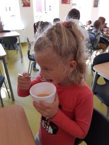 Uczennica oddziału przedszkolnego uchwycona z profilu podczas jedzenia łyżeczką musu ze styropianowej miseczki.