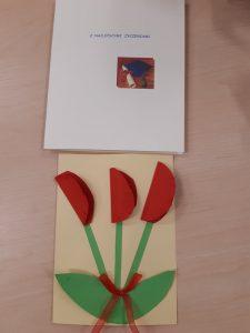 """Zdjęcie dwóch kartek ułożonych jedna pod drugą. Na kartce u góry napis """"Z najlepszymi życzeniami"""" oraz zdjęcie niebieskiego biretu wraz z zwiniętą w rulon i przewiązana czerwoną wstążką kartką. A pod spodem kartka z wyklejonymi trzema kwiatkami. Na zielonych łodygach przewiązanych czerwoną książką umieszczono zgięte w pół, czerwone koła imitujące kwiaty."""