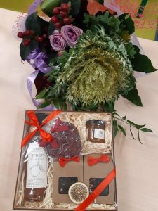 Zdjęcie prezentu otrzymanego przez wychowawczynię oddziału Przedszkolnego od wychowanków - kwiaty i eleganckie pudełko przewiązane czerwoną wstążką z butelką, słoiczkiem oraz dwoma papierowymi torebkami.