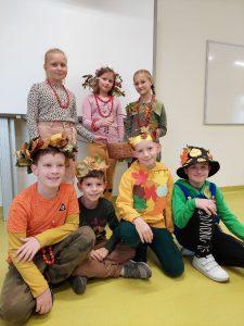 Uczniowie klasy trzeciej pozują do zdjęcia w swojej sali. Czterech chłopców siedzących w pierwszym rzędzie ma na głowie korony bądź kapelusze z liści a trzy dziewczynki stojące za nimi mają na szyjach korale z jarzębiny.
