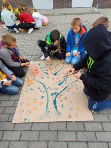 Uczniowie klasy trzecie klęczą na chodniku wokół dużego kawałka brystolu, na którym rysują drzewo z kolorowymi liściami. W tle widać grupkę dziewczynek zgromadzonych wokół swojej kartki. papieru.