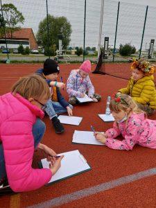Uczniowie z klasy trzeciej siedzą bądź leżą na boisku szkolnym. Każdy z nich ma przed sobą kartkę i cos do pisania na niej.