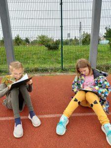 Uczennice klasy trzeciej siedza na szkolnym boisku i wykonują rysunki. Swoje prace przymocowane do czarnych podkładek opierają na kolanach.