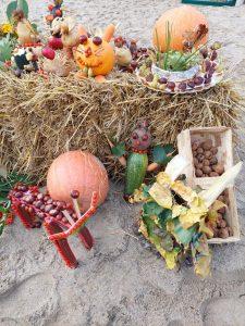 Plony jesieni ułożone na sześciennych belach słomy. Wśród nich kasztany, żołędzie i dynie ułożone osobno oraz figurki zwierząt z nich zrobione.