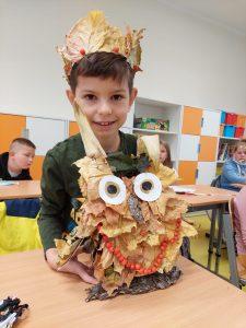 Uczeń klasy trzeciej prezentuje wykonaną pzrze siebie z liści, jarzębiny i kory sowę. Na głowie ma koronę z liści.