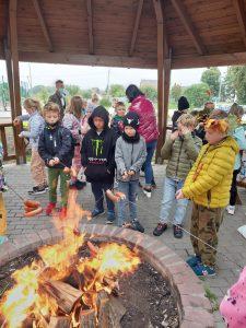 Uczniowie klasy trzeciej stoją wokół ogniska i smażą kiełbaski.