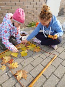 Dwie uczennice z klasy trzeciej siedzą na chodniku i układają kolorowe liście w ramce stworzonej z patyków i leżącej przed nimi.