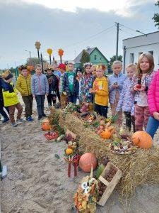 Uczniowie klasy trzeciej pozują do zdjęcia ustawieni w okół belek siana, na jtórych zostały poukładane naturalne dary jesieni.