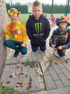 Trzech uczniów klasy trzeciej klęczy na chodniku. Przed nimi leży ułożona z patyków ramka a w niej żołędzie i kasztany. Chłopiec po prawej stronie ma na głowie kapelusz przybrany kolorowymi liśćmi