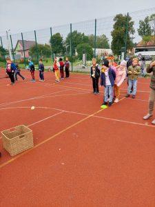 Uczniowie klasy trzeciej grają w gry na boisku szkolnym. Na pierwszym planie widzimy kosz oraz uczniów ustawionych w rzędzie przed nim.
