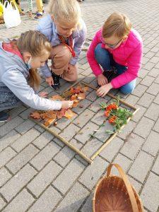 Trzy dziewczynki klęczą na chodniku i układają liście w ramce utworzonej z patyków.