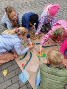 Uczennice z klasy trzeciej pochylaja się nad wykonywaną wspólnie pracą - rysunkiem kolorowego drzewa.