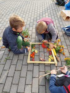 Dwóch chłopców z klasy trzeciej klęczy na chodniku przed ułożoną z listewek ramką. Wewnątrz ramki chłopcy układają liście i jarzębinę.