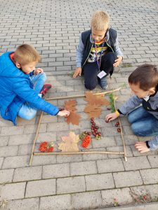 Trzech uczniów klasy trzecie klęczy na chodniku. Przed nimi leży ułożona z patyków ramka a w niej liście, żołędzie i jarzębina.
