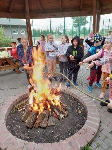 Uczniowie klasy trzeciej stoją wokół ogniska i smażą w nim kiełbaski .