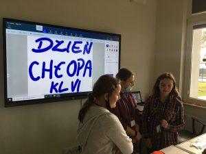 """TRzy uczennice stoją obok siebie. W tle na ścianie zawieszony jest ekran interaktywny, na którym wy swietla sie odręczny napis """"DZIEŃ CHŁOPA KL VI""""."""