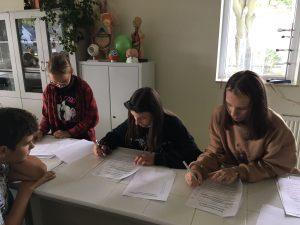 Trzy uczennice siedzą przy stoliku i trzymają w dłoniach długopisy. Przed nimi leżą zapisane kartki papieru. Po drugiej stronie stolika siedzi uczeń opierający głowę na przedramieniu.