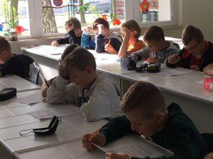 Chłopcy z klasy szóstej siedzą w ławkach i rozwiazują test przygotowany dla nich przez koleżanki.