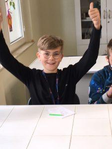Uczeń z klasy szóstej szeroko uśmiecha się do zdjęcia z podniesionymi w górę rękoma.