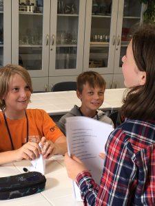 Dwóch chłopców z klasy szóstej uśmiecha się do koleżanki stojącej przed nimi i trzymającej w dłoniach zapisane kartki.