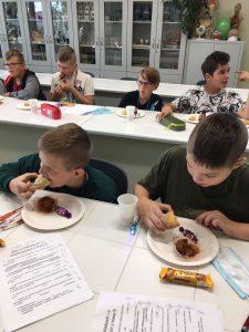 Chłopcy z klasy szóstej siedzą przy stolikach i kedzą ciastka leżące na telarzykach przed nimi.