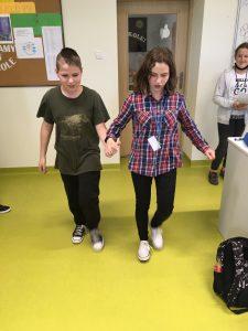 Para uczniów z klasy szóstej trzyma się za ręce i idzie przez salę lekcyjną.