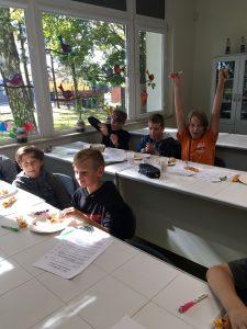 Chłopcy z klasy szóstej siedzą w ławkach. Jeden z nich ma wyciągnięte w góre ręce. Przed nimi stoją talerze ze słodyczami, kartki papieru oraz piórniki.