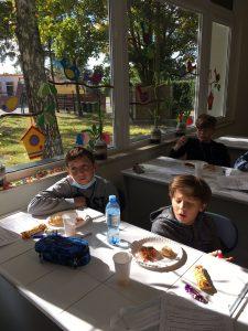Uczniowie klasy szóstej siedzą przy stolikach,. Przed nimi stoi butelka z wodą, talerzyki z ciastem, cukierki i niebieski piórnik.
