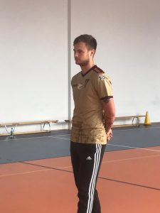 Pan Maciej Żurawski stoi z rękami złożonymi za plecami na sali gimnastycznej.