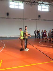 Pan Maciej Zurawski oraz uczeń szkoły stoją do siebie plecami na sali gimnastycznej. W tle widać innych uczniów.