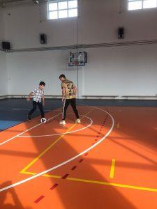 Uczeń szkoły oraz Pan Maciej Żurawski w trakcie gry na szkolnej hali sportowej.