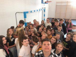 Uczniowie szkoły zgromadzeni wokół Pana Maćka Żurawskiego rozdającego autografy na szkolnej hali sportowej.