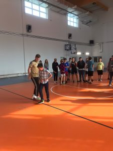 Pan Maciej Żurawski gra w piłkę nożną z jednym z uczniów na szkolnej sali gimnastycznej.