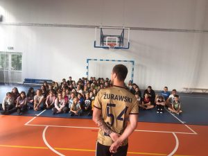 Pan Maciej Żurawski stoi na przeciw uczniów siedzących na podłodze sali gimnastycznej.