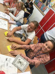 Uczniowie pracuje przy swoich projektach na zajęciach z techniki. Dwie uczennice z pierwszego planu uśmiechaja sie do zdjęcia jednocześnie trzymając w dłoniach swoje materiały.